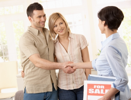 Estate agent congratulating young couple on making deal on new house.