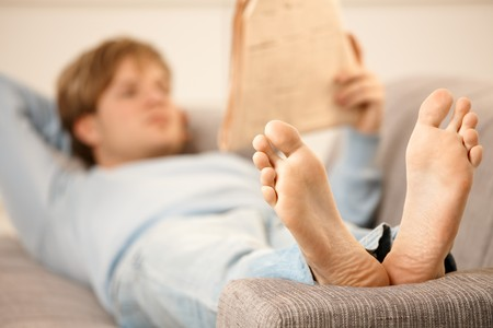 Man lying on back on sofa reading newspaper, focus on bare feet.