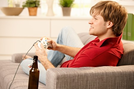 Young man sitting on sofa playing computer game, smiling,
