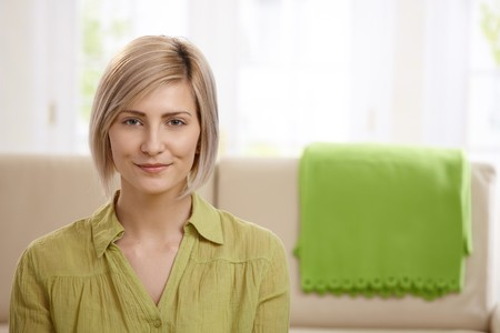 Portrait of attractive blonde woman smiling at home, sofa in background.