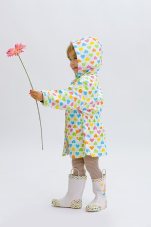Small girl wearing raincoat and boots, giving pink flower to somebody. Isolated on white background.