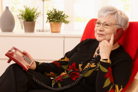 Pensioner woman using landline phone sitting in armchair in living room.