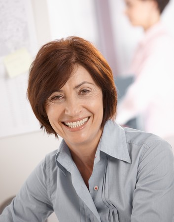 Portrait of senior businesswoman smiling at camera, coworker in background.