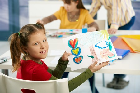 Portrait of elementary age schoolgirl showing colorful paining to camera in art class in primary school classroom.