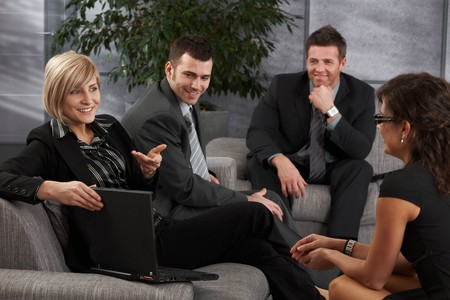 Satisfied businesspeople sitting on couch in office, businesswoman explaining.