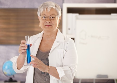 Senior teacher standing in classroom, holding test tube, teaching chemistry in elementary school.