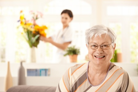 Portrait of happy elderly woman sitting on sofa at home, nurse arranging flowers in background.