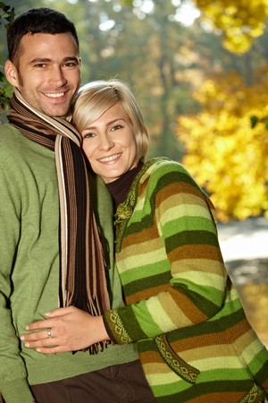 Portrait of happy young love couple in autumn park looking at camera, smiling.