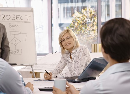 Smiling mid adult businesswoman sitting on team meeting, looking at camera.