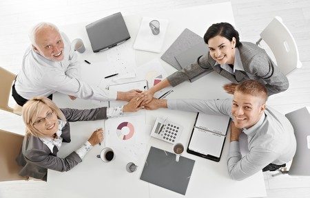 Confident businessteam holding hands at meeting over table expressing teamwork and unity, smiling at camera, overhead view.