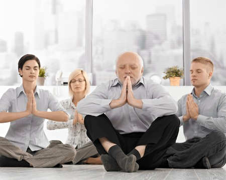 Businesspeople doing meditation in office with closed eyes, hands put together, concentrating.
