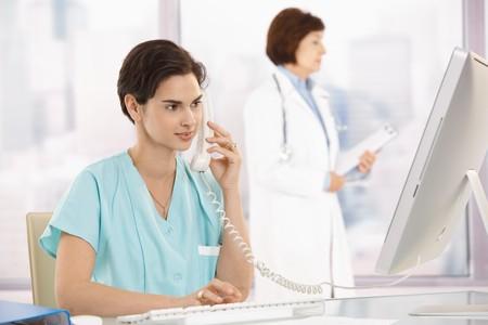 Medical assistant sitting at desk, talking on landline phone, using computer, doctor in background.