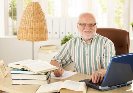 Portrait of senior professor sitting at desk, doing research work, using laptop computer, smiling at camera.