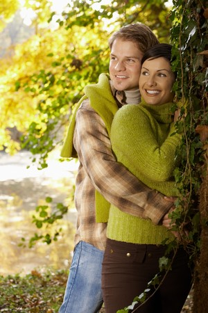 Portrait of happy young couple in autumn park standing at tree, laughing.
