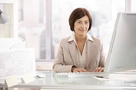 Portrait of senior businesswoman sitting at office desk, smiling at camera.