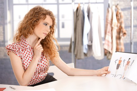 Foto de Young attractive fashion designer working in office at desk thinking. - Imagen libre de derechos