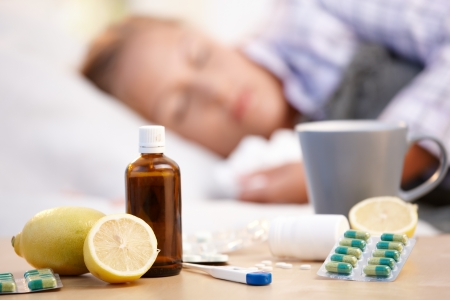 Vitamins, medicines and hot tea in front, woman caught cold sleeping in background.