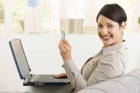 Young woman using laptop computer, showing up flash drive, smiling.