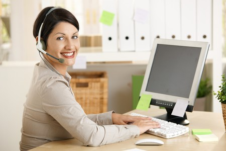 Happy assistant talking on headset, typing on computer in office.