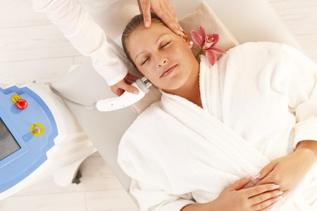 Young woman getting radio frequency fat reduction treatment in day spa, smiling.