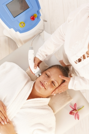Young woman getting radio frequency cellulite treatment in day spa.