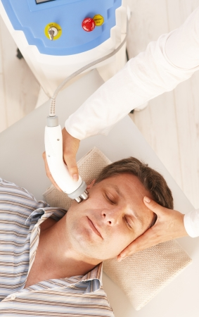 Man getting radio frequency fat reduction treatment in day spa.