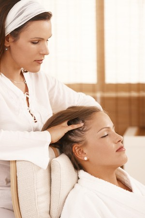 Woman getting relaxing head massage with closed eyes.