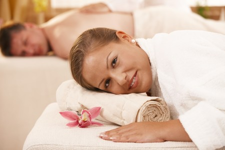 Relaxed couple lying on massage bed in day spa.