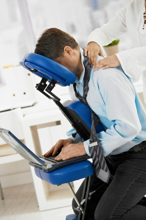 Businessman sitting on massage chair, getting back massage.