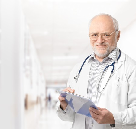 Portrait of senior doctor on hospital corridor holding clipboard looking at camera smiling.