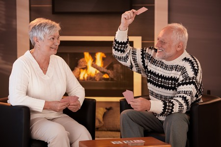 Retired couple playing cards in front of fireplace in living room at home, smiling.の写真素材