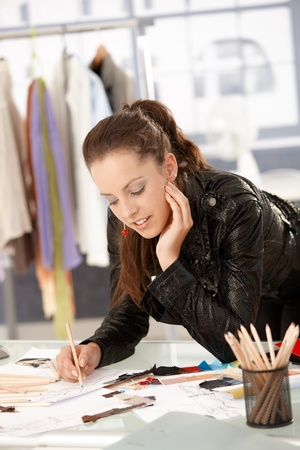Attractive fashion designer working in office, leaning on desk, drawing.