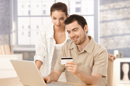 Happy couple using laptop, shopping online at home, using credit card.