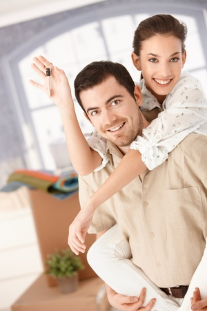 Photo pour Happy couple moving house, boxes around, holding keys, smiling, having fun. - image libre de droit