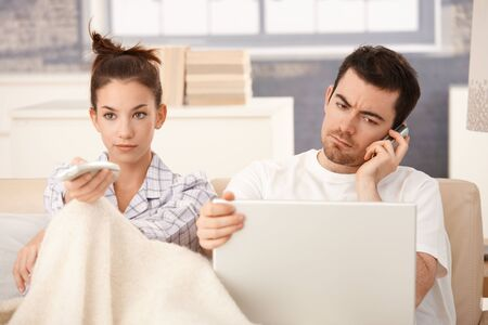 Young couple in bed, man using laptop and mobile, woman watching television.の写真素材