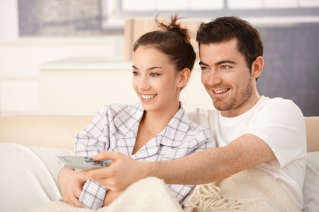 Happy couple watching television in bed, hugging each other, smiling.