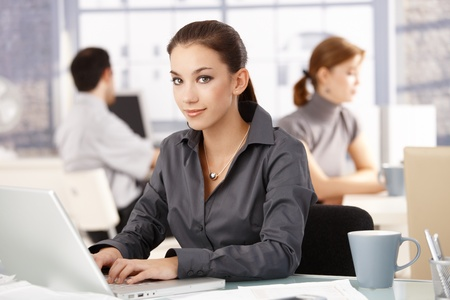 Young attractive businesswoman sitting at desk in office, colleagues working in the background.