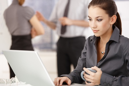 Young attractive woman working on laptop in office, colleagues standing in background.