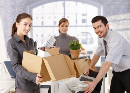 Young office workers moving office, unpacking boxes, smiling.
