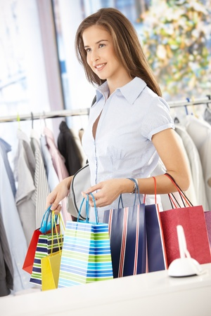 Portrait of shopping girl standing in clothes store, holding shopping bags.