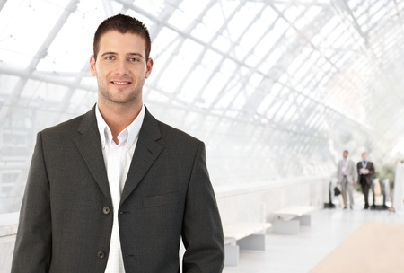 Photo pour Young businessman standing in bright office lobby smiling at camera. - image libre de droit