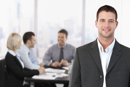 Photo pour Portrait of young confident businessman in meeting room, with colleagues in background. - image libre de droit