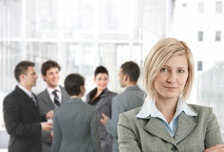 Photo pour Smiling businesswoman in office lobby, colleagues talking in background. - image libre de droit