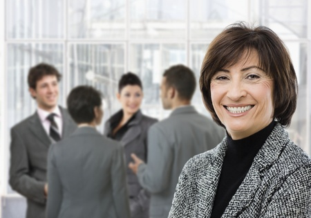 Senior businesswoman smiling, looking at camera, businesspeople in conversation in lobby.
