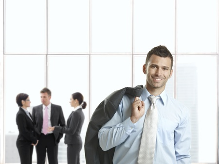 Photo pour Happy businessman in office lobby smiling at camera, businesspeople talking in background. - image libre de droit
