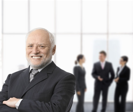 Portrait of smiling senior businessman standing with arms folded, businesspeople in background.の写真素材