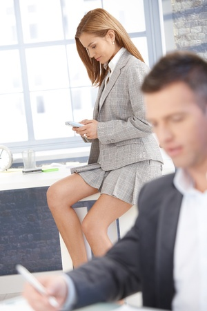 Sexy businesswoman in mini skirt texting in office, businessman working at desk.