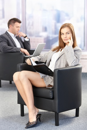 Sexy businesswoman sitting in office lobby during conference break, looking at organizer.の写真素材