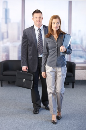 Photo pour Manager and assistant going to business meeting, smiling. - image libre de droit