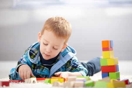 Lovely toddler boy playing with building cubes at home, laying on floor.